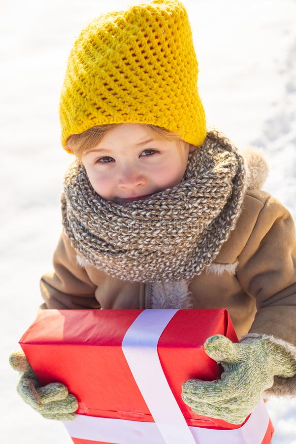 Happy winter child hold gift bow snow background. Small boy wear winter clothes hat and scarf close up. Happy new year. And merry christmas. Winter holidays royalty free stock images