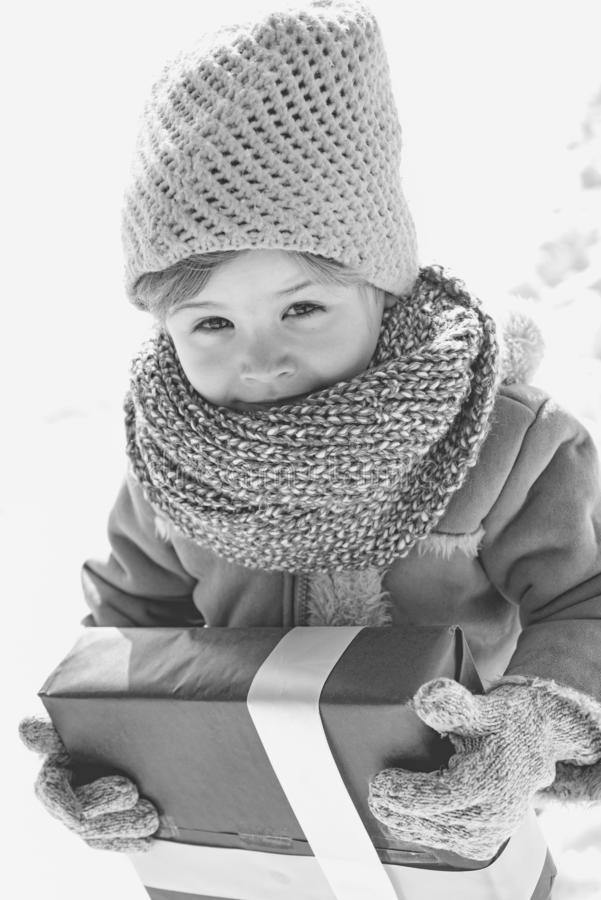 Happy winter child hold gift bow snow background. Small boy wear winter clothes hat and scarf close up. Happy new year. And merry christmas. Winter holidays stock photography
