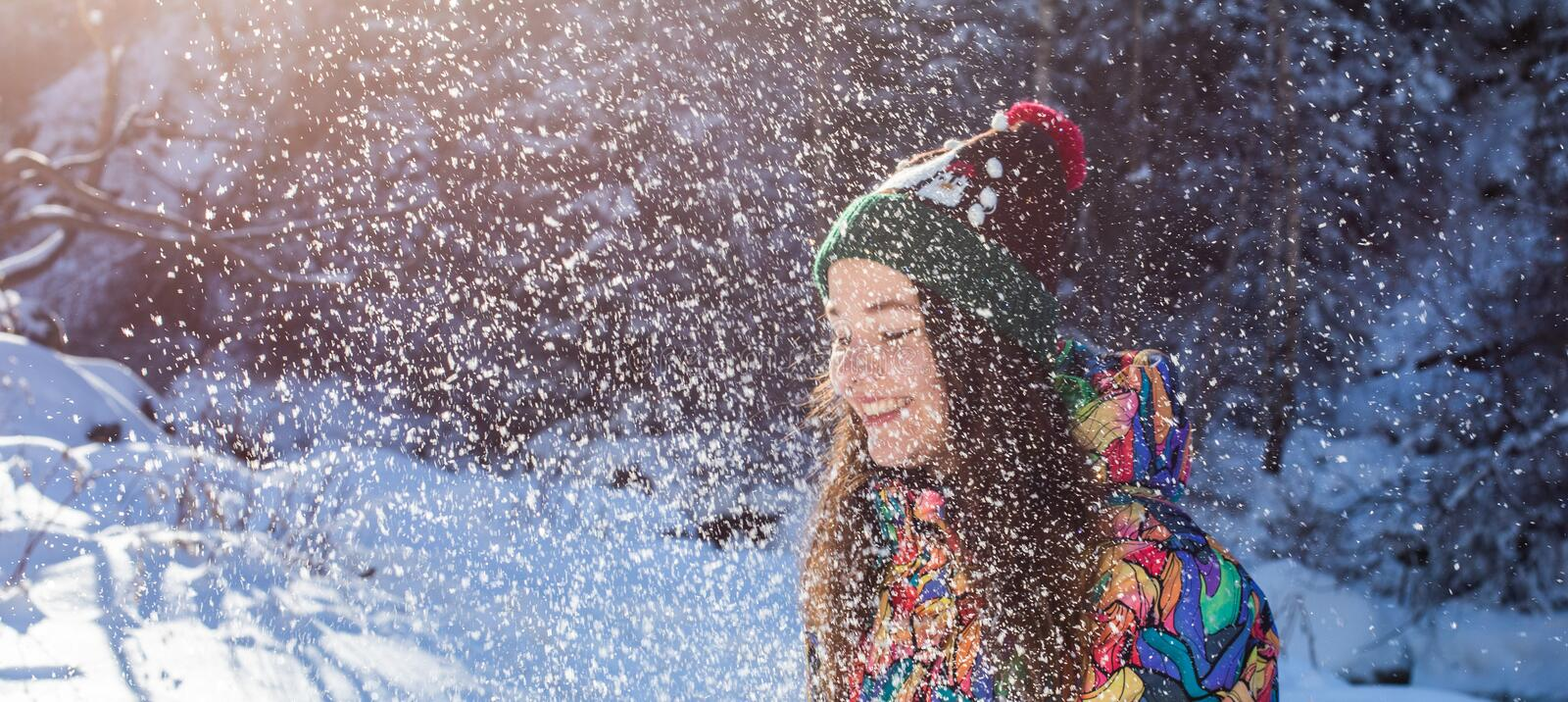Happy winter fun woman throwing snow banner. Panorama crop of outdoor lifestyle girl playing in snow outside laughing in royalty free stock image