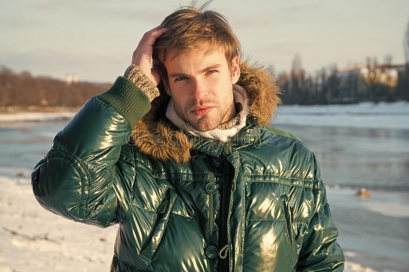 Happy winter holidays. Flu and cold. Winter fashion. Green warm coat. Warm clothes for cold season. Man traveling in stock photo