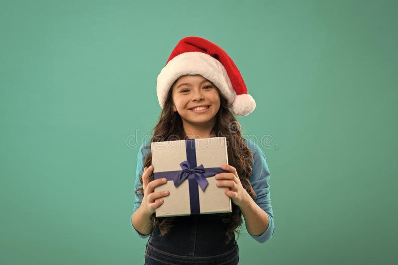 Happy winter holidays. Small girl. Little girl child in santa hat. New year party. Santa claus kid. Present for Xmas royalty free stock photography