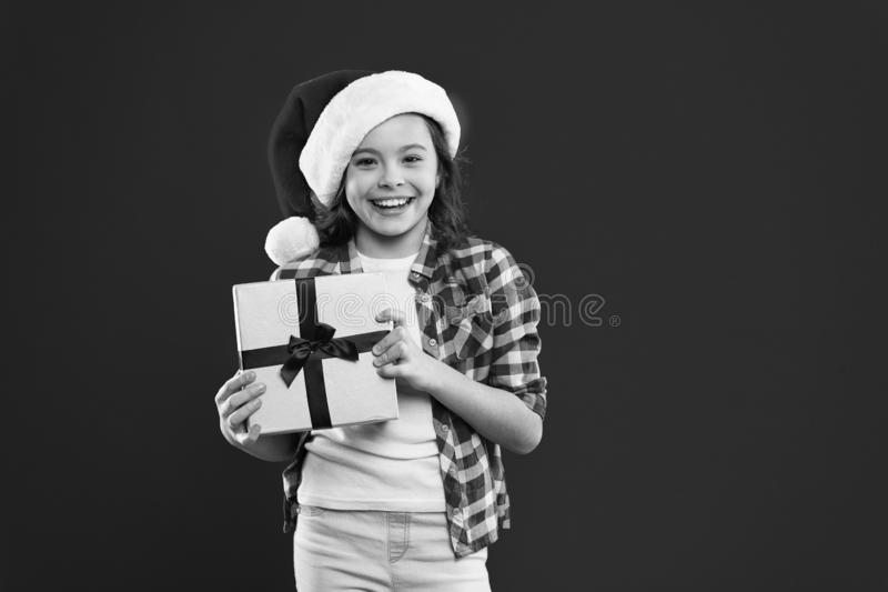 Happy winter holidays. Small girl. Present for Xmas. Childhood. Christmas shopping. Little girl child in santa red hat royalty free stock images