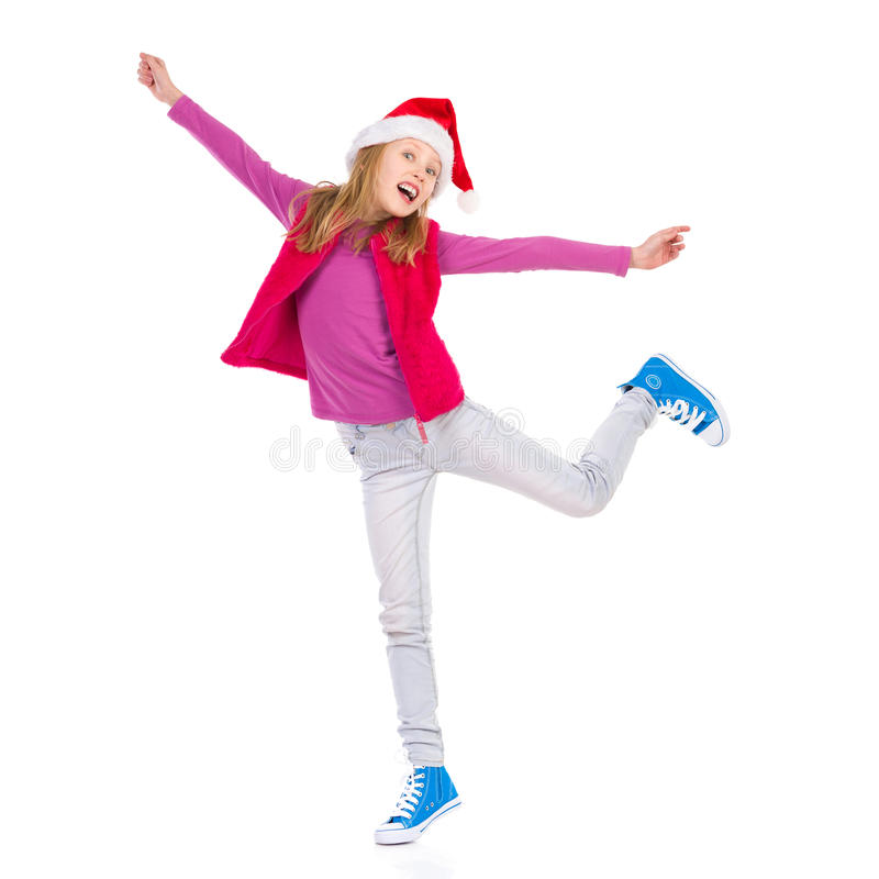 Happy Winter Little Girl. Excited Girl in Santa's hat is standing on one leg with arms outstretched. Full length length studio shot isolated on white royalty free stock photography