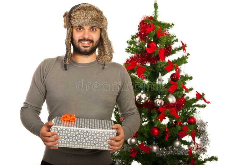 Happy winter man with gift. Happy winter man holding Christmas gift in front of tree royalty free stock image