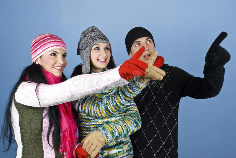 Happy winter people pointing up royalty free stock photography