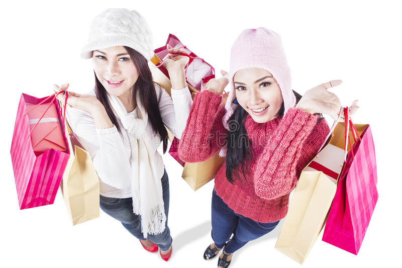 Happy winter shopping with friends - isolated. Two happy friends do shopping together, isolated in white royalty free stock photo