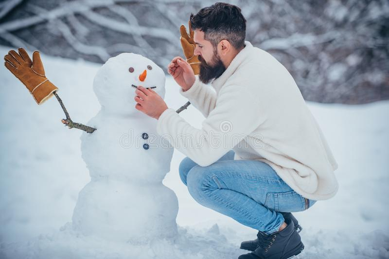 Happy winter time. Winter concept. Snowman and funny bearded man the friend is standing in winter hat and scarf with red royalty free stock images