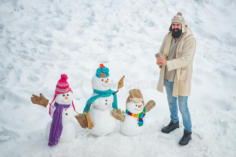 Happy winter time. Fashion portrait of young model man indoors with Christmas snowman. Handsome Winter Man with snowman royalty free stock images