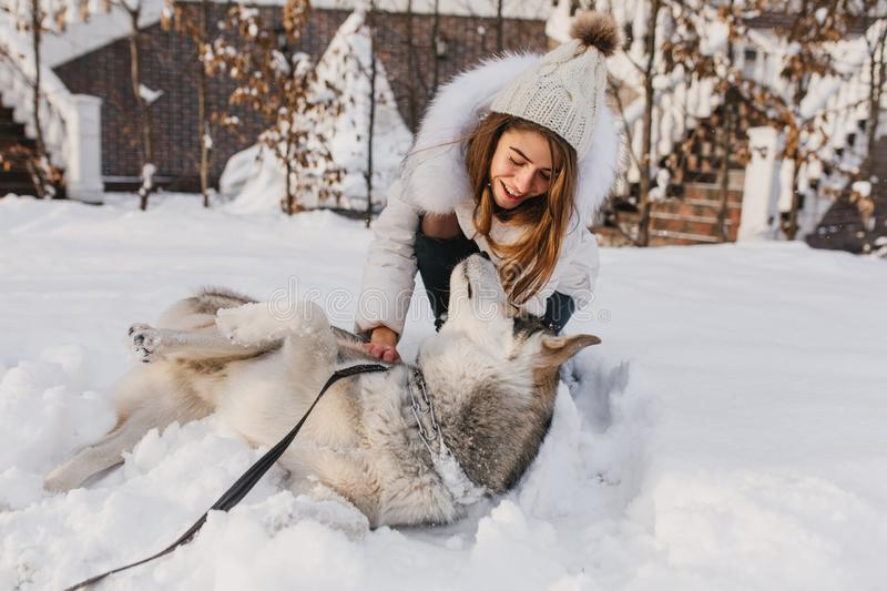 Happy winter time of joyful young woman playing with cute husky dog in snow on street. Cheerful mood, positive emotions stock photo