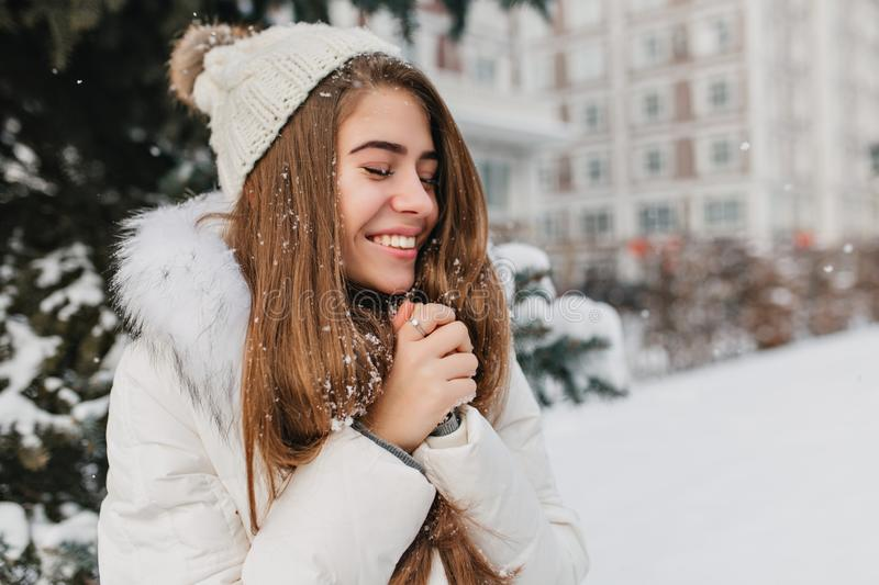 Happy winter time of young joyful woman enjoying snow in city. Attractive girl, long brunette hair, smiling with closed stock images