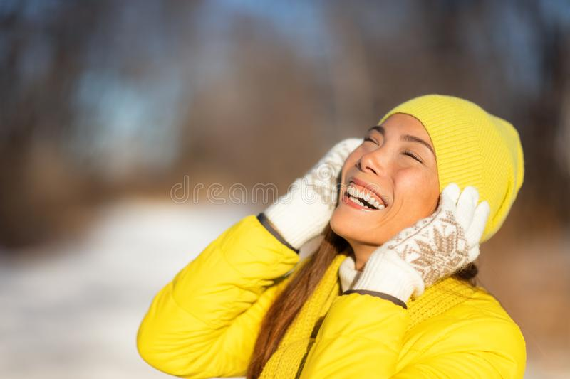 Happy winter woman enjoying cold with yellow hat protecting ears, gloves, coat for frost protection. Asian girl smiling stock photos