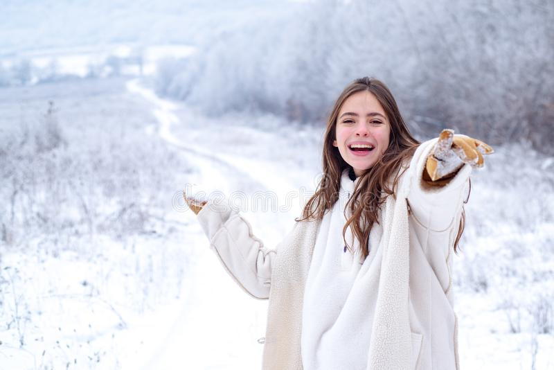 Happy winter woman on on snowy background. Outdoor beautiful girl with long hair wearing sweater posing in street of stock photography