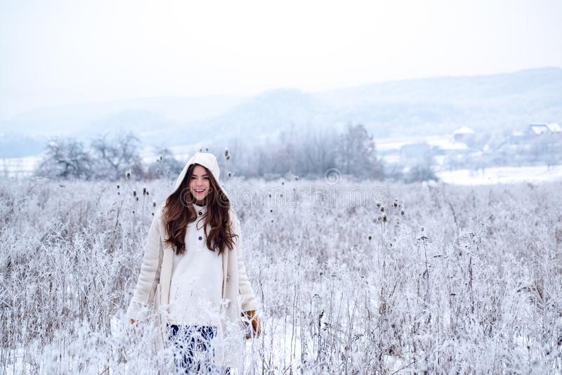 Happy winter woman on on snowy background. Outdoor beautiful girl with long hair wearing sweater posing in street of stock photo
