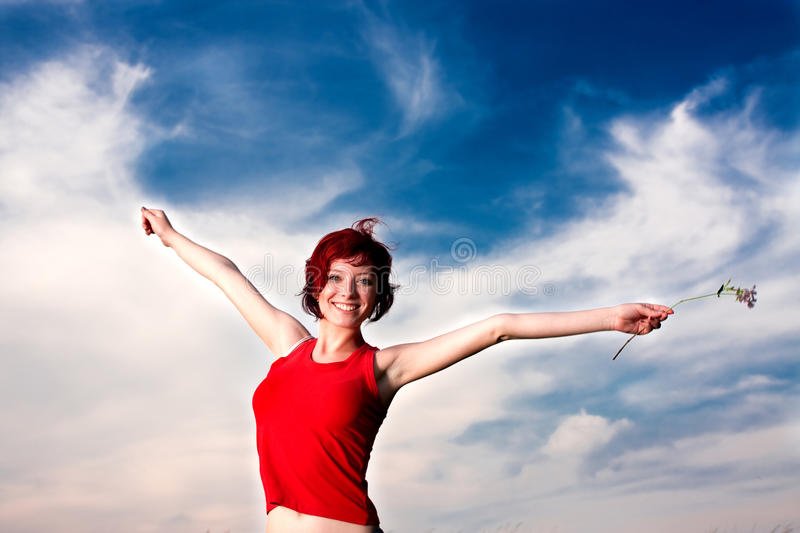Happy Woman. A happy woman in red holding a flower, on the backdrop of blue sky stock photography