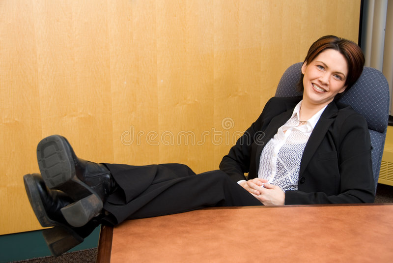 Happy woman. Relaxed business woman with her feet up royalty free stock photography
