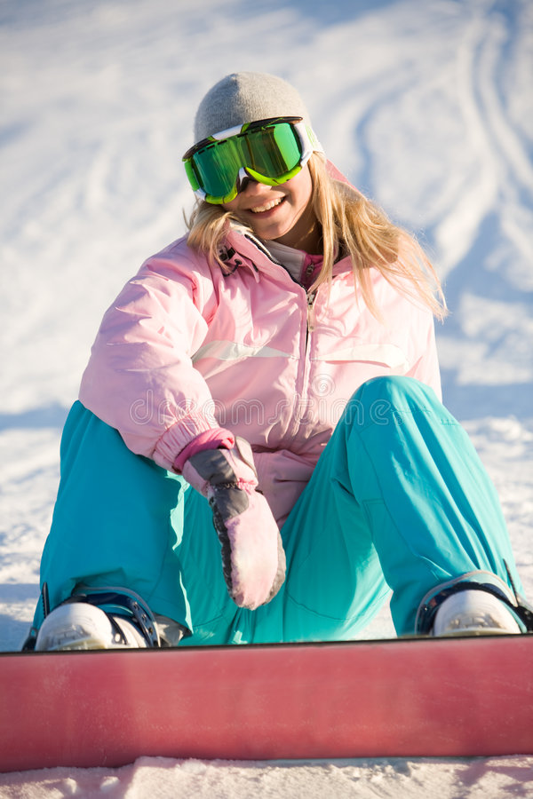 Happy woman. Photo of laughing female wearing snowboarding clothes sitting on ground stock photography