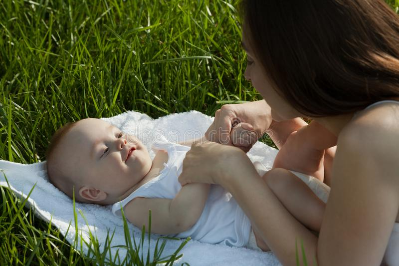 Happy woman with adorable baby lying on the grass. Happy family. royalty free stock photography