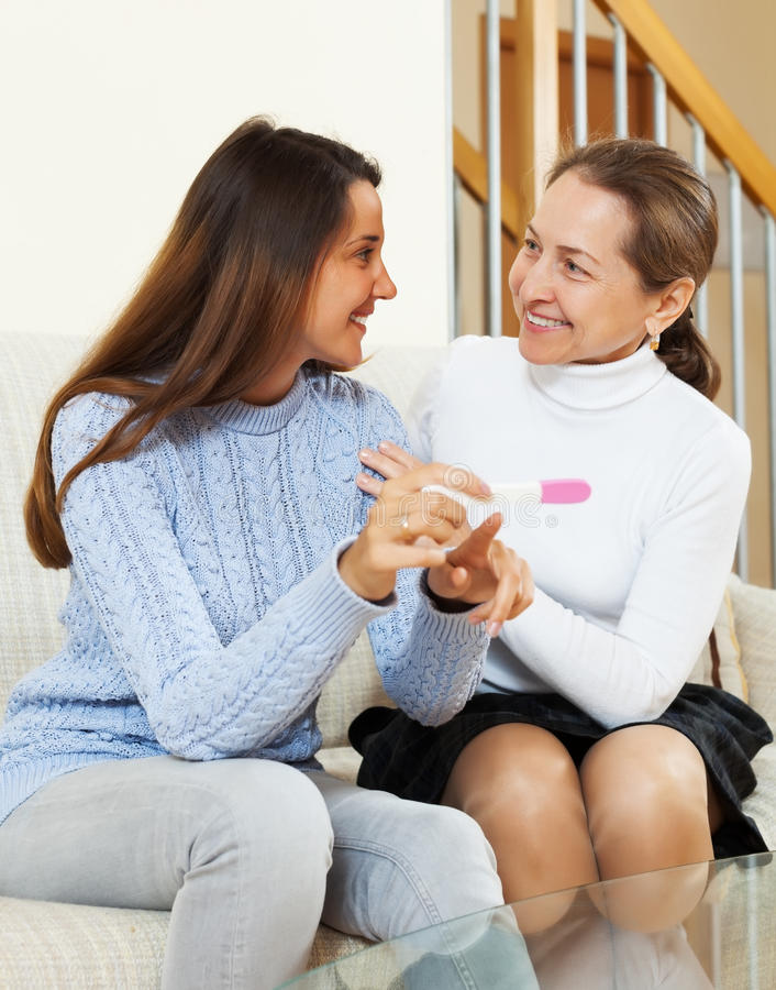 Happy woman and adult daughter with pregnancy test. Happy women and adult daughter with pregnancy test at home interior royalty free stock photos