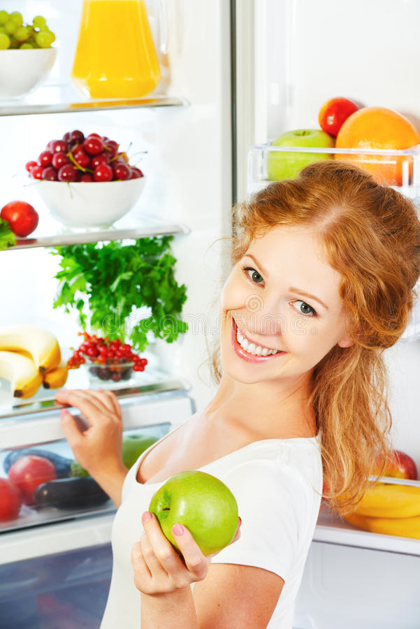 Happy woman with apple and open refrigerator with fruits, vegetables and healthy food royalty free stock images