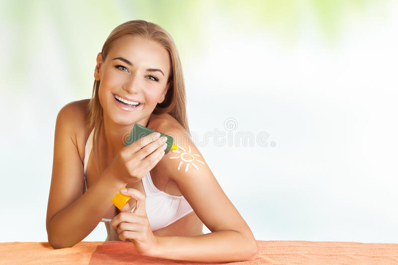 Happy woman applying sunscreen royalty free stock image