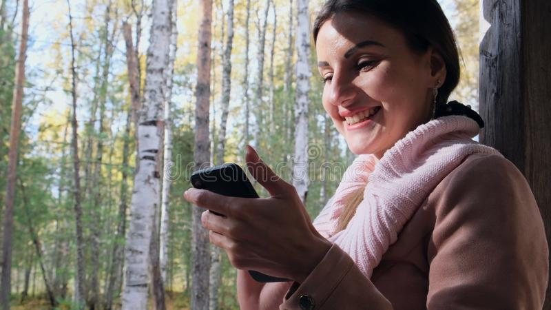 Happy woman in the autumn forest talking on the phone, sends messages on a smartphone, reads something on a mobile phone stock image