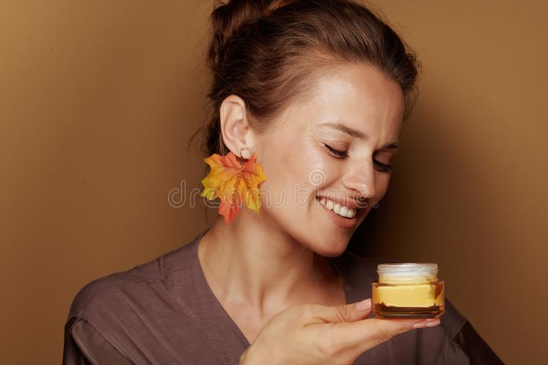 Happy woman with autumn leaf earring holding facial creme royalty free stock photography