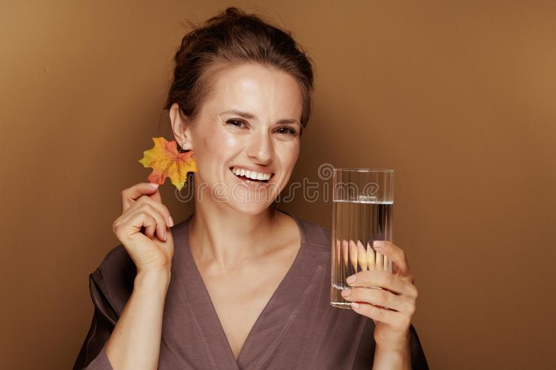 Happy woman with autumn leaf earring holding glass of water royalty free stock image