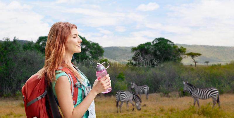 Happy woman with backpack over african savannah. Adventure, travel, tourism, hike and people concept - smiling young woman with backpack and bottle of water over royalty free stock images
