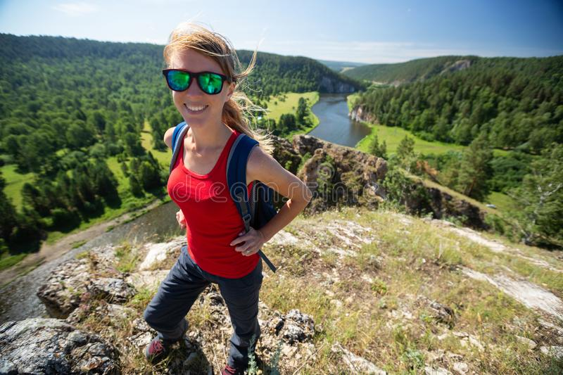Happy woman with backpack. Stands on the hill with valley on the background stock images