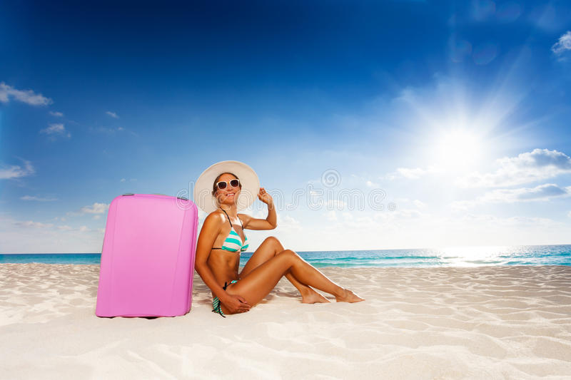 Happy Woman With Baggage On The Beach Stock Photo