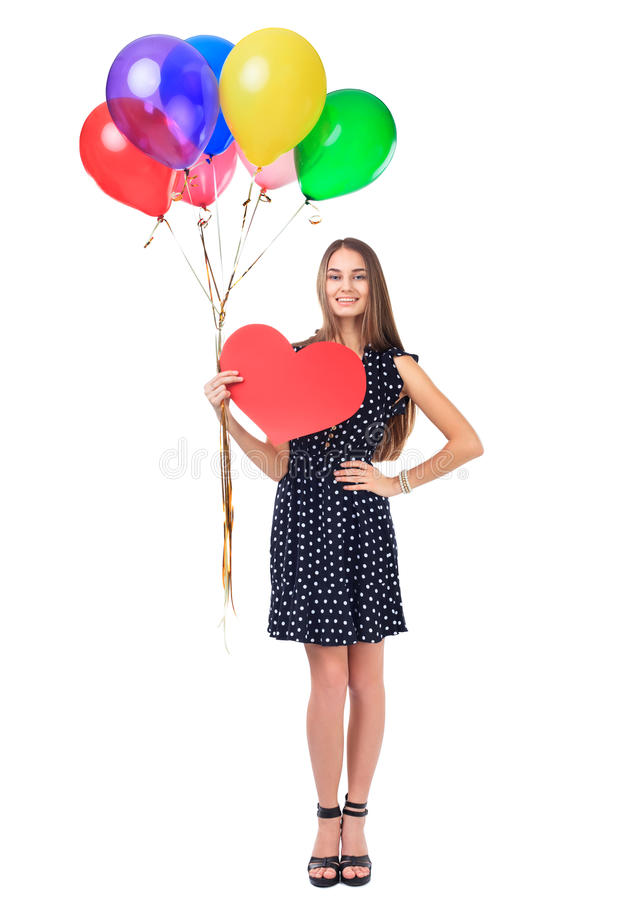 Happy woman with balloons and red heart. Full length portrait of beautiful smiling young woman in polka dot dress holding colorful balloons and red heart stock image