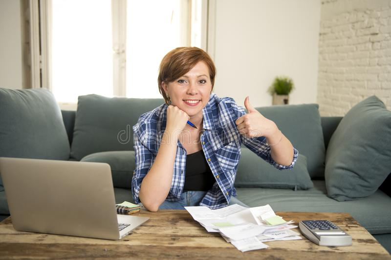 Happy woman banking and accounting home monthly and credit card expenses with computer laptop doing paperwork royalty free stock photography