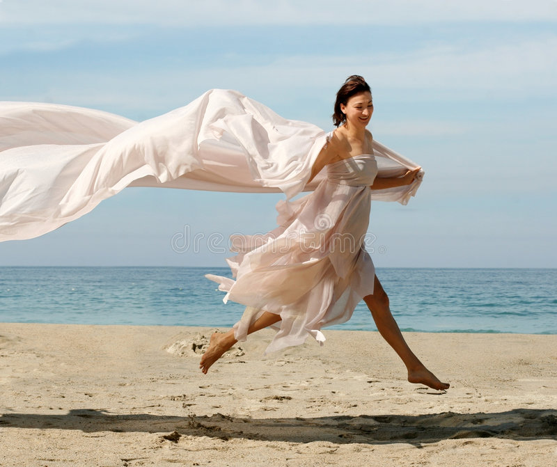 Happy woman on the beach. Happy woman with a scarf on the beach stock photos