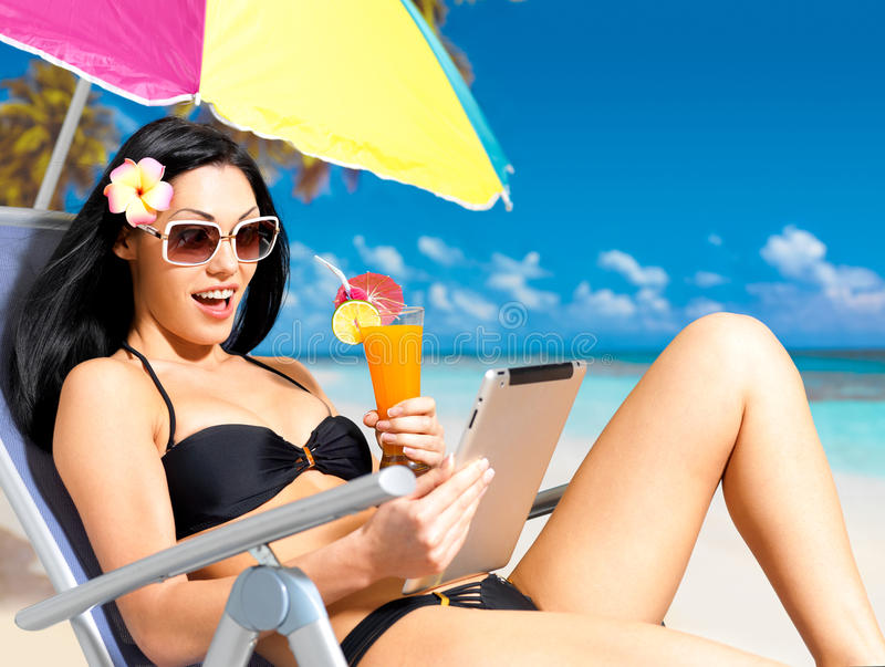Happy woman on the beach with ipad royalty free stock image