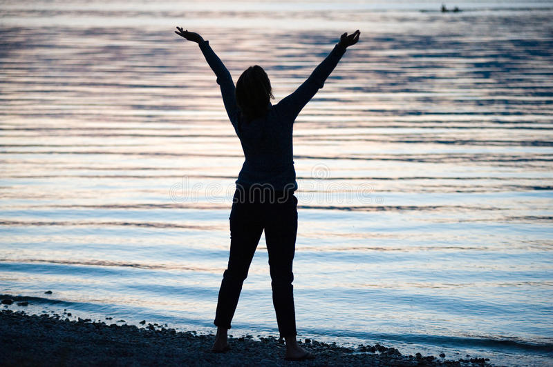 Happy woman on beach. A happy woman on the beach of a lake in the evening stock image