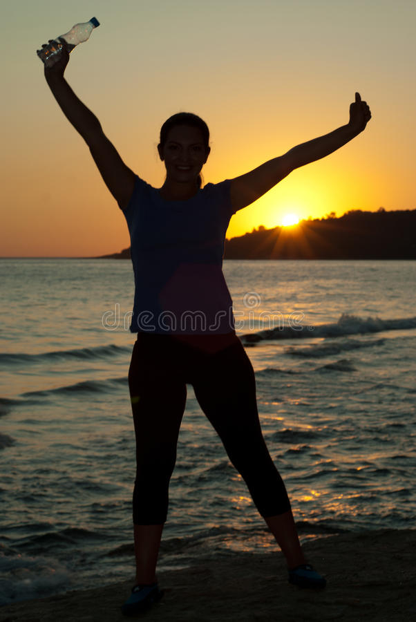 Happy woman on beach at sunset
