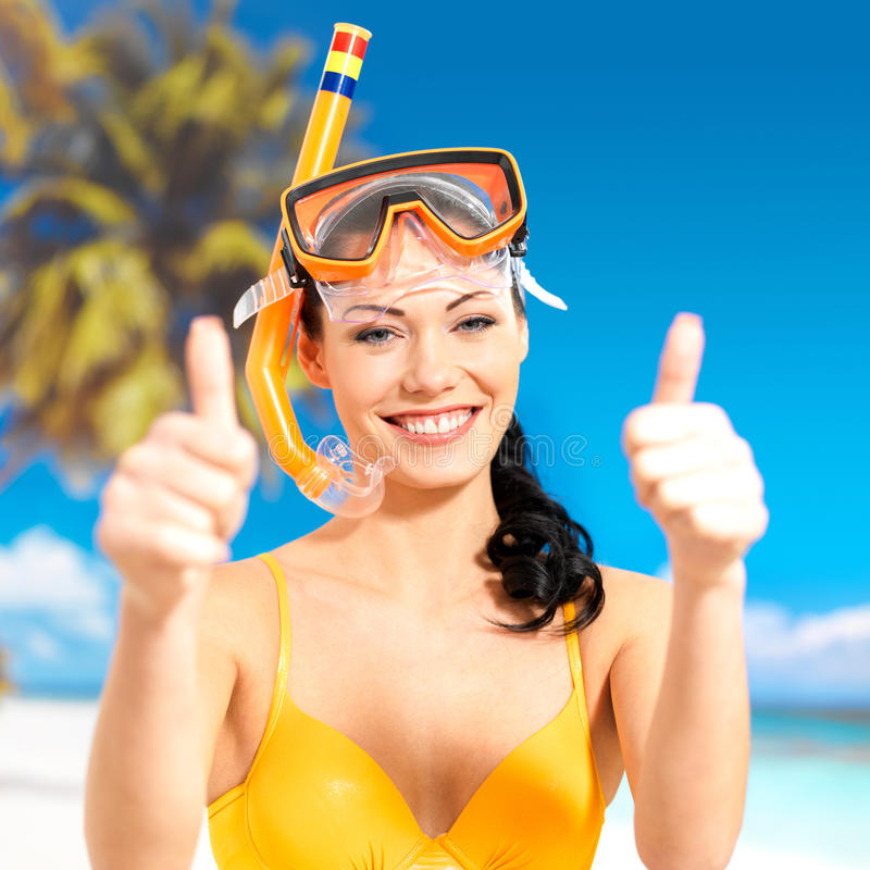 Happy woman on beach with thumbs up sign