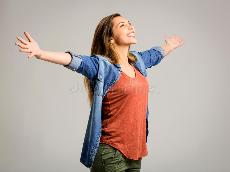 Happy woman. Beautiful happy woman with arms up over a gray background stock image