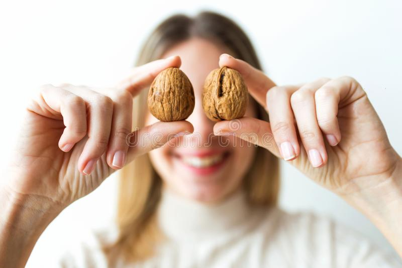 Happy woman with beautiful healthy mouth holding walnuts front of eyes on white background stock image