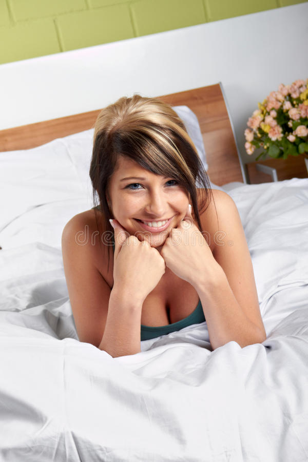 Happy woman on bed stock images
