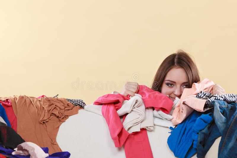 Happy woman behind sofa in messy room at home stock photography