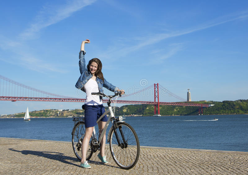 Happy woman with bicycle. The girl in a denim jacket, white T-shirt and blue shorts with a bike is on the waterfront in Lisbon near the red bridge names on April royalty free stock images
