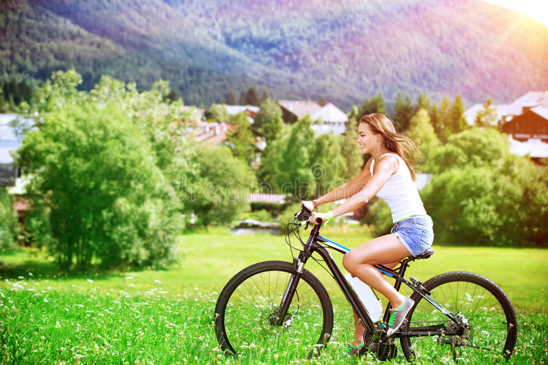 Happy woman on a bicycle stock photo