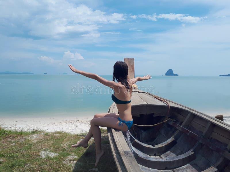 Happy young woman in bikini sitting on a boat stock photo