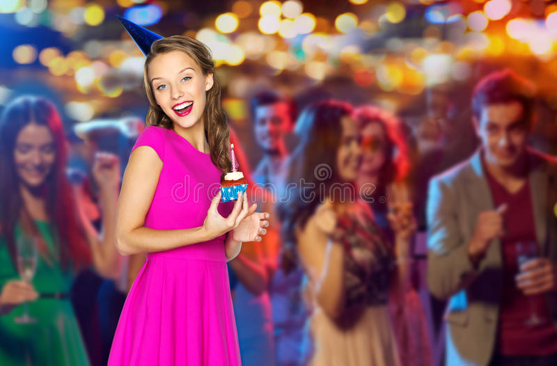 Happy woman with birthday cupcake at night club. People, holidays and celebration concept - happy young women or teen girl in pink dress and party cap with stock photos