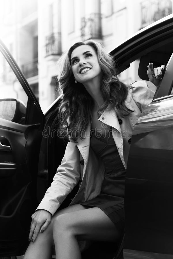Happy woman. Black and white portrait of a beautiful successful woman, sitting in the car, smiling and dreaming royalty free stock photography