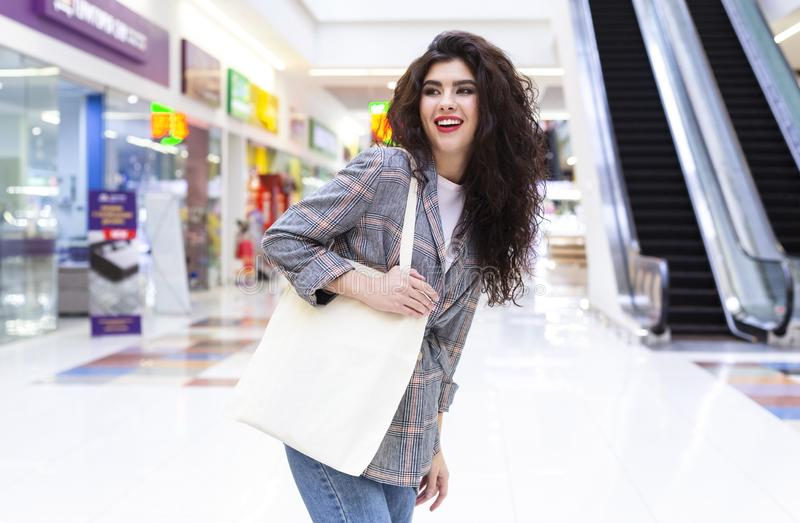 Happy woman with blank eco bag shopping in city mall. Happy woman with blank eco cotton bag shopping in city mall and waiting for friend stock photography
