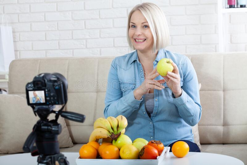 Happy woman blogger shows fruits to the camera at home stock photos