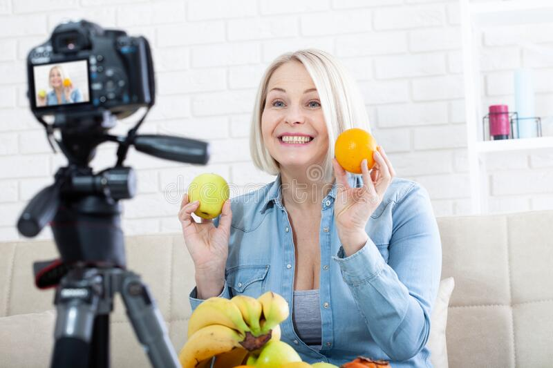 Happy woman blogger shows fruits to the camera at home royalty free stock image