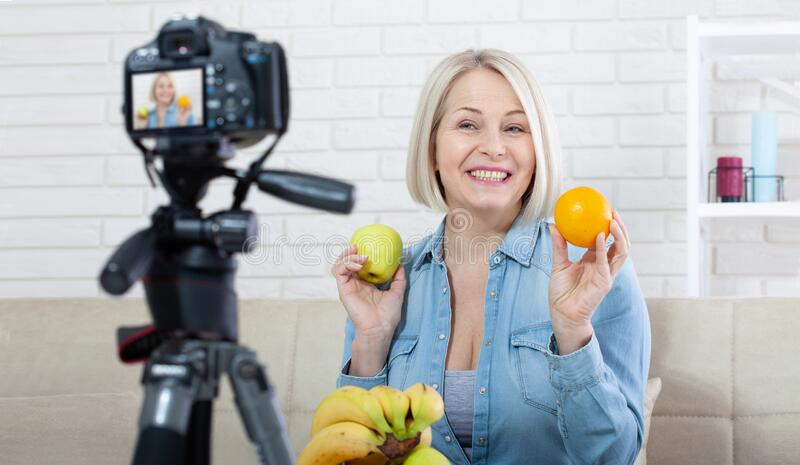 Happy woman blogger shows fruits to the camera at home royalty free stock images